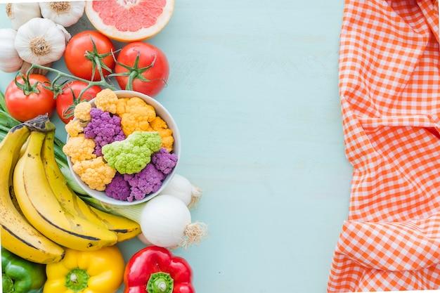 Eine obenliegende ansicht des gesunden gemüses und der serviette über dem farbigen hintergrund Kostenlose Fotos