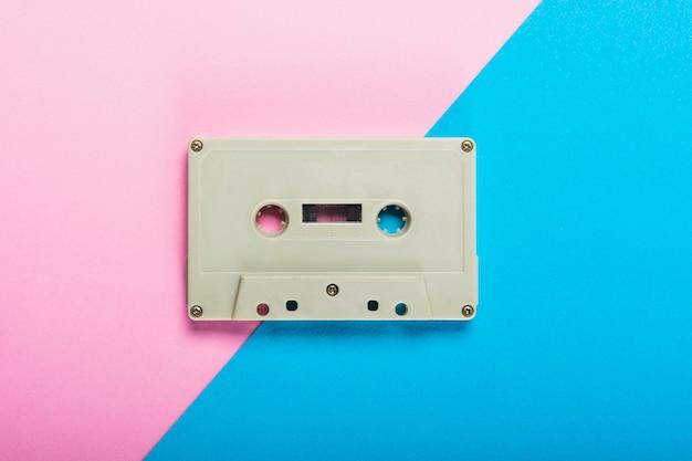 Eine obenliegende ansicht des kassettenbandes auf dem doppelten rosa und blauen hintergrund Kostenlose Fotos