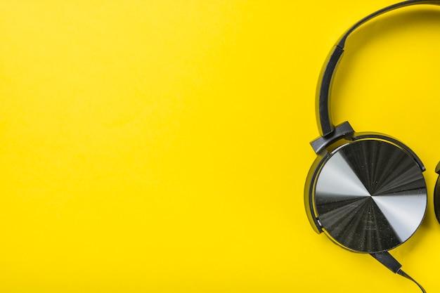 Eine obenliegende ansicht des kopfhörers auf gelbem hintergrund Kostenlose Fotos