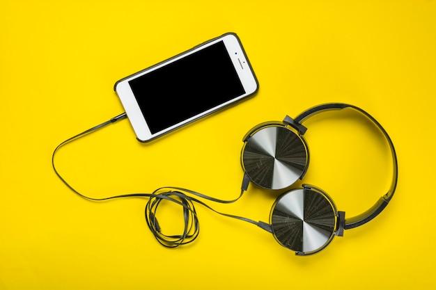 Eine obenliegende ansicht des kopfhörers befestigt mit mobiltelefon auf gelbem hintergrund Kostenlose Fotos