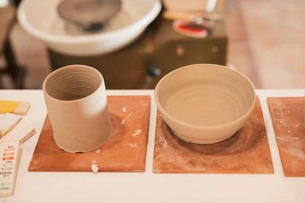 Eine obenliegende ansicht des lehmglases und der schüssel auf tabelle in der werkstatt Kostenlose Fotos