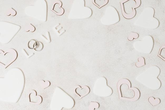 Eine obenliegende ansicht des liebestextes mit den diamanthochzeitsringen umgeben mit rosa und weißer herzform Kostenlose Fotos
