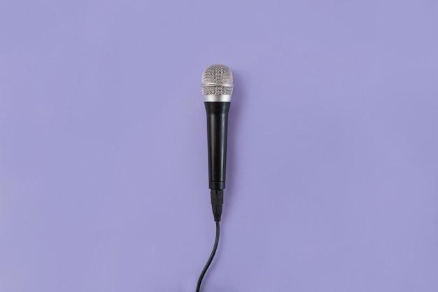 Eine obenliegende ansicht des mikrofons auf purpurrotem hintergrund Premium Fotos