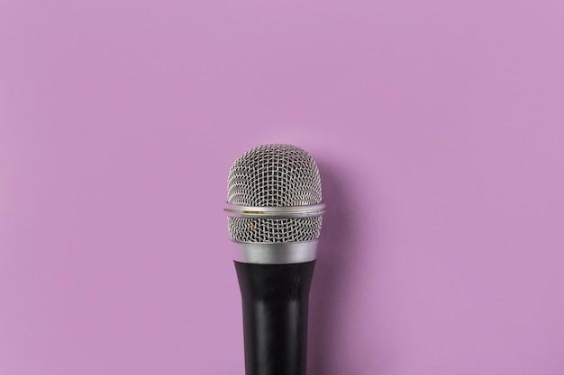 Eine obenliegende ansicht des mikrofons auf rosa hintergrund Kostenlose Fotos