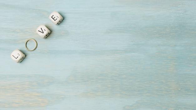 Eine obenliegende ansicht des textes gemacht mit würfeln und ehering auf der ecke des hölzernen hintergrundes Kostenlose Fotos