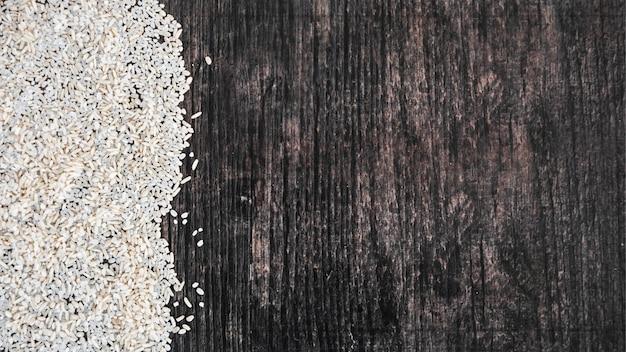 Eine obenliegende ansicht des ungekochten weißen reises auf schwarzem hölzernem strukturiertem hintergrund Kostenlose Fotos