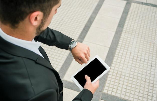 Eine obenliegende ansicht eines geschäftsmannes, der in der hand seinen uhrholdinghandy betrachtet Kostenlose Fotos