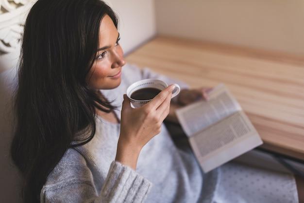 Eine obenliegende ansicht eines mädchens, das buch trinkenden kaffee hält Kostenlose Fotos