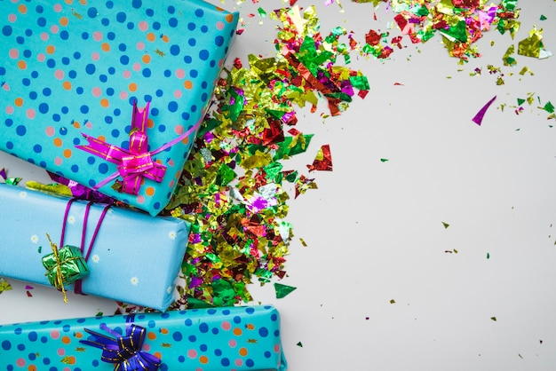 Eine obenliegende ansicht von eingewickelten geschenkboxen mit bunten konfettis auf grauem hintergrund Kostenlose Fotos