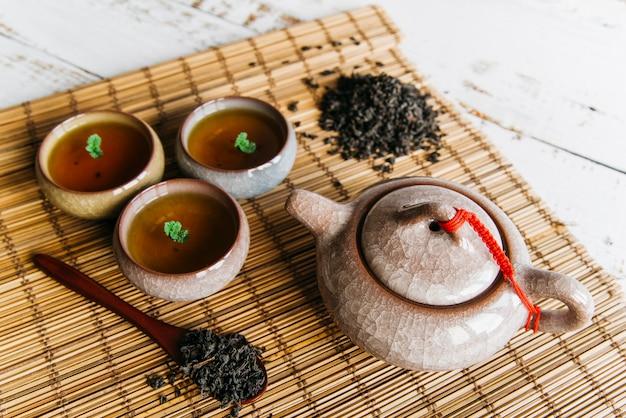 Eine obenliegende ansicht von kräuterteetassen und von teekanne mit getrockneten teeblättern auf tischset Kostenlose Fotos