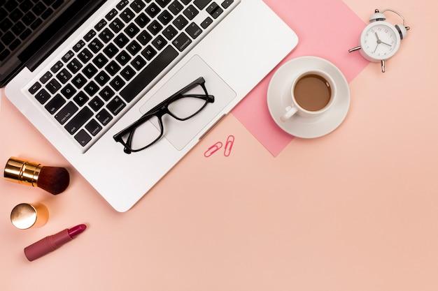 Eine obenliegende ansicht von make-upkosmetikprodukten, von brillen, von laptop, von kaffeetasse und von wecker auf pfirsichhintergrund Kostenlose Fotos