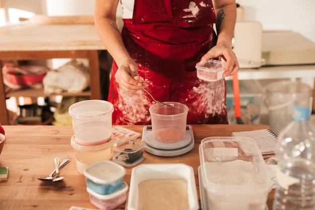 Eine obenliegende ansicht von weiblichen tonwaren das farbpulver messend Kostenlose Fotos