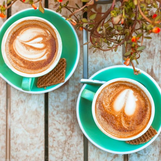 Eine obenliegende ansicht von zwei kaffeetasse mit herzform lattekunst Kostenlose Fotos