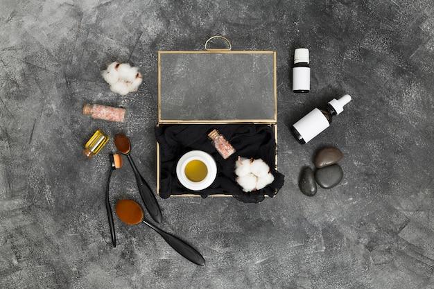 Eine offene kiste mit honig; rosa himalayasalz und baumwollknospe mit kosmetikprodukten auf konkretem schwarzem hintergrund Kostenlose Fotos