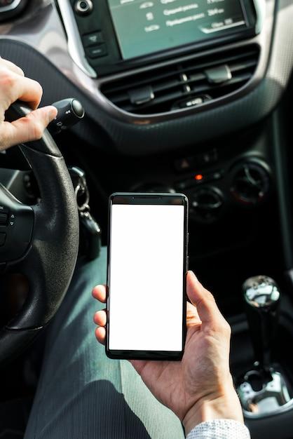Eine person, die das auto hält handy mit weißem bildschirm fährt Kostenlose Fotos