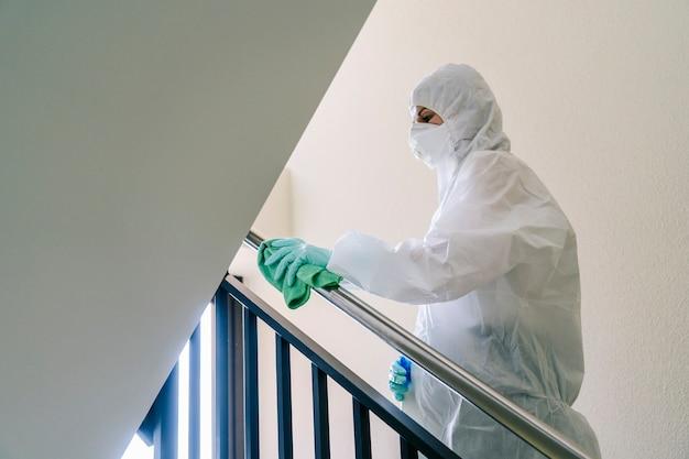 Eine person, die mit sicherheitskleidung vor einer pandemie oder einem virus geschützt ist, reinigt und desinfiziert ein portal eines hauses Premium Fotos