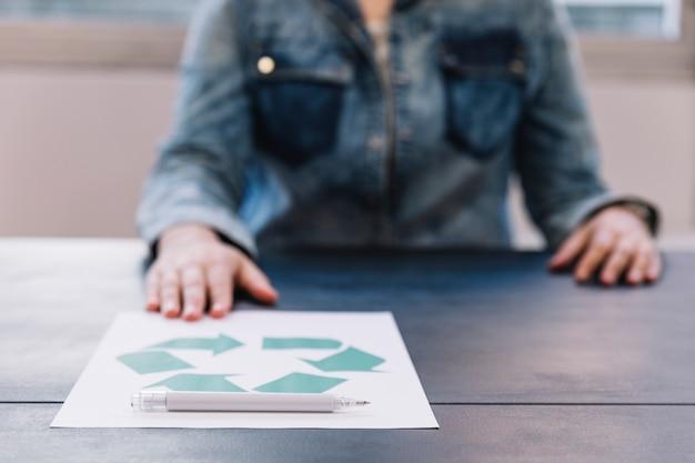 Eine person, die recyclingpapier mit stift auf holztisch zeigt Kostenlose Fotos