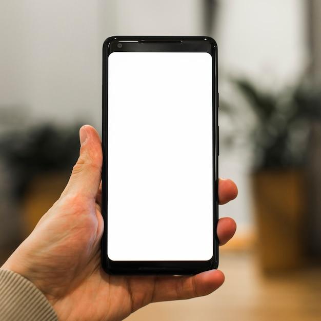 Eine person, die sein neues smartphone vor unscharfem hintergrund bewirbt Kostenlose Fotos