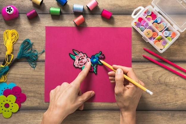 Eine person, die umriss um den flecken auf rosa papier zeichnet Kostenlose Fotos