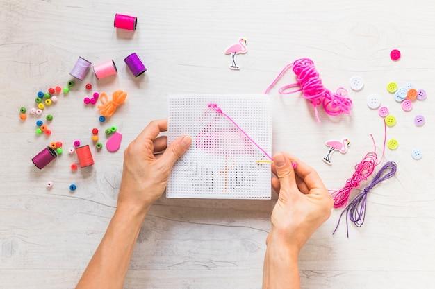 Eine person kreuzstich-stickerei mit zahnseide thread und dekorative elemente Kostenlose Fotos