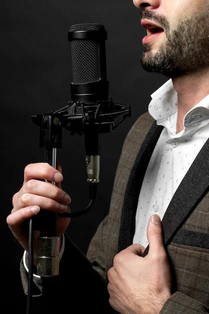 Eine person singt vor stehendem mikrofon Kostenlose Fotos