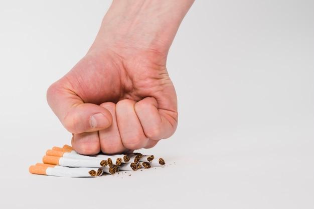 Eine personenfaust, welche die zigaretten lokalisiert auf weißem hintergrund zerquetscht Kostenlose Fotos