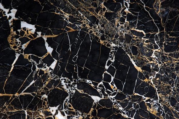 Eine platte aus schwarzem marmor mit wunderschönen gelben und weißen adern namens new portoro. Premium Fotos