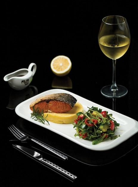 Eine platte des gegrillten lachsfilets mit gewürzen und grünem salat diente mit einem glas italienischem wein Kostenlose Fotos