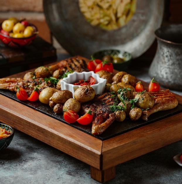 Eine platte mit gegrilltem rindfleisch, kartoffeln und gemüse auf einem steintisch Kostenlose Fotos