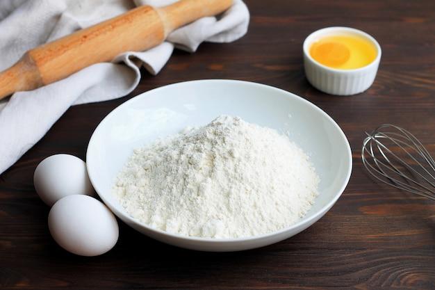 Eine platte mit mehl, eiern, einem nudelholz und wischen auf einem weißen hölzernen hintergrund. Premium Fotos