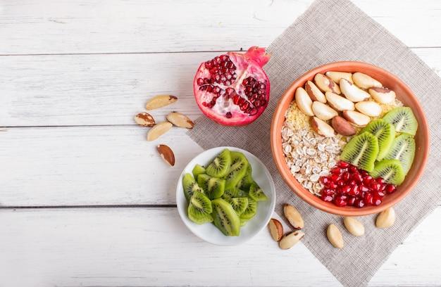 Eine platte mit müsli, kiwi, granatapfel, paranüsse auf einem weißen hölzernen hintergrund. Premium Fotos