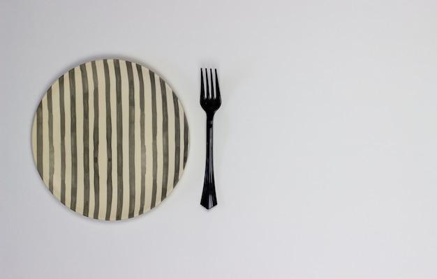 Eine platte und eine gabel auf einem weißen hintergrund. minimalismus. Premium Fotos