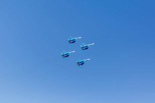 Eine quadratische formation einer gruppe von vier russischen militärkampfflugzeugen, die hoch in den blauen himmel fliegen Premium Fotos