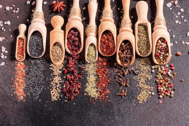Eine reihe von gewürzen und kräutern. indische küche. pfeffer, salz, paprika, basilikum. ansicht von oben. Premium Fotos