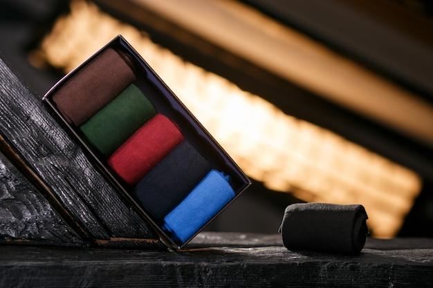 Eine reihe von klassischen socken in einem schwarzen geschenkpaket Premium Fotos