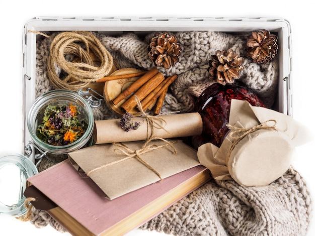 Eine reihe von nützlichen zutaten für die behandlung zu hause. marmelade und trockene kräuter zum aufbrühen von tee. buch und umschlag. gemütliche atmosphäre im winter und herbst Premium Fotos