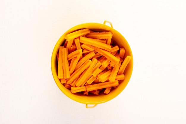 Eine rohe orangenpasta der italienischen trockenen nudeln der draufsicht in der schüssel auf dem weiß Kostenlose Fotos