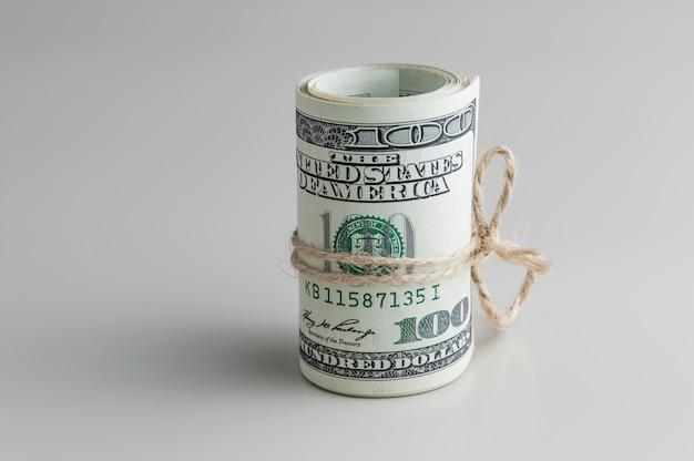 Eine rolle von hundert dollarscheinen gebunden mit einem seil auf einem grauen hintergrund. seitenansicht. Premium Fotos