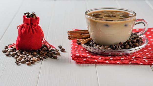 Eine rote tasche füllte mit kaffeebohnen und einer schale eiskaffee und zimt auf einer weißen tabelle. Premium Fotos
