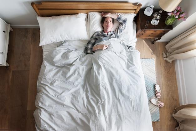 Eine schlaflosigkeitsfrau auf bett Premium Fotos