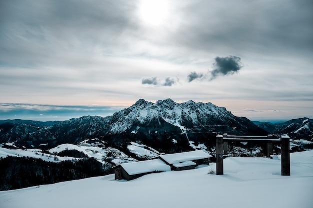 Eine schneebedeckte hütte mit einem schönen blick auf schneebedeckte berge Kostenlose Fotos