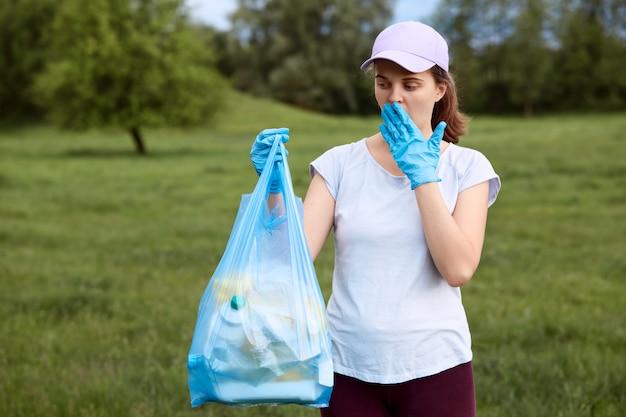 Eine schockierte dame, die ihren mund bedeckt, während sie den blauen müllsack voller müll betrachtet, sammelt sich auf der wiese Kostenlose Fotos