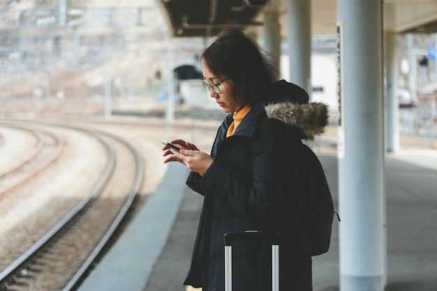 Eine schöne asiatische frau benutzt ein smartphone im stadtzentrum, um zu suchen Premium Fotos
