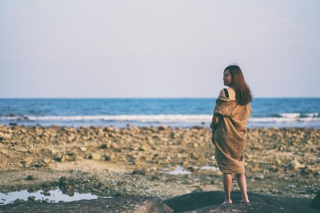 Eine schöne asiatische frau, die am strand an der küste spaziert Premium Fotos