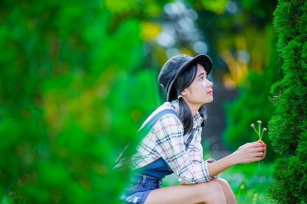 Eine schöne asiatische frau, die einen hut trägt, um im grünen garten als hintergrund sich zu entspannen und zu genießen. Kostenlose Fotos