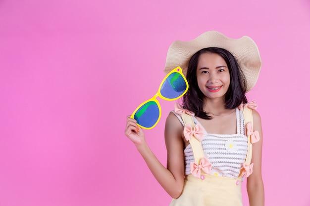 Eine schöne asiatische frau, die einen hut und große gläser mit einem rosa trägt. Kostenlose Fotos