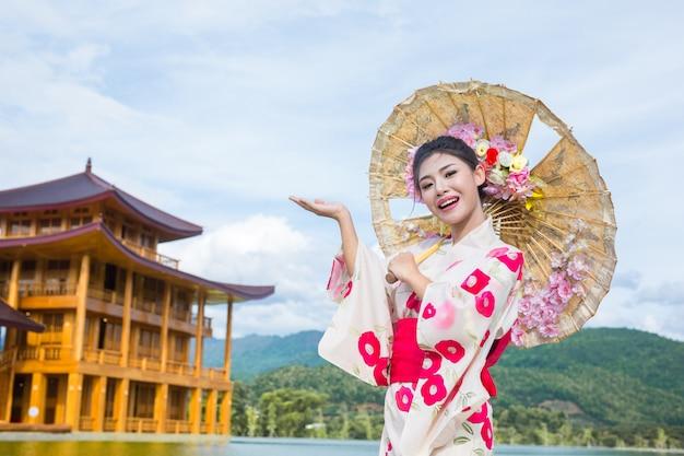 Eine schöne asiatische frau, die einen japanischen kimono, traditionelles kleidkonzept trägt. Kostenlose Fotos