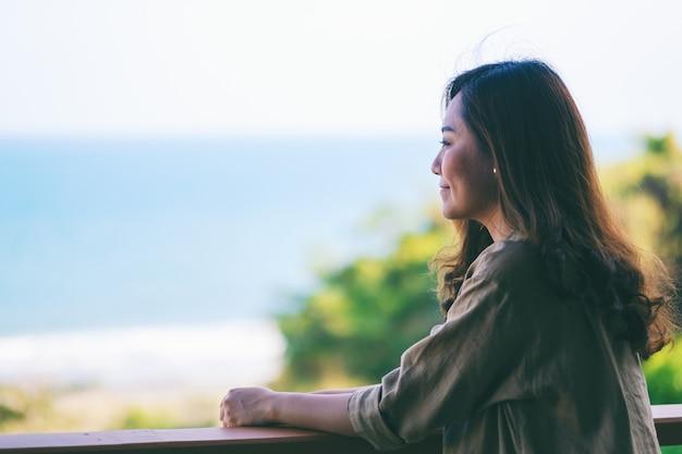 Eine schöne asiatische frau, die steht und genießt, den meerblick auf balkon zu beobachten Premium Fotos