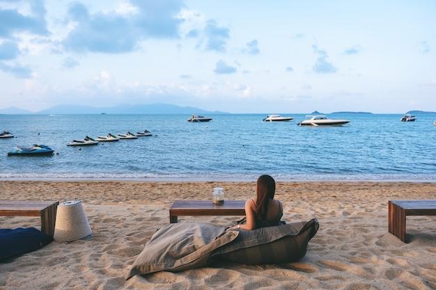 Eine schöne asiatische frau genießt es, am strand am meer zu sitzen und zu entspannen Premium Fotos