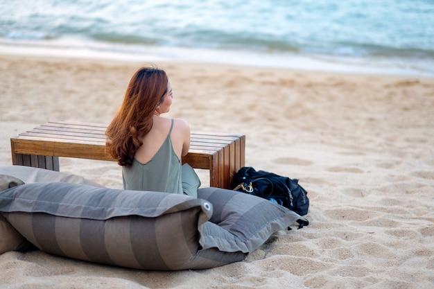 Eine schöne asiatische frau genießt es, am strand am meer zu sitzen Premium Fotos